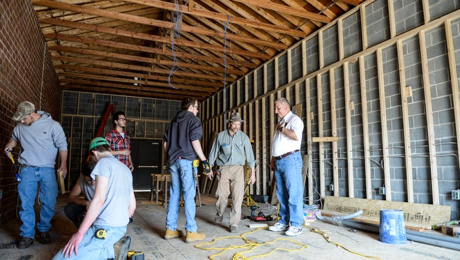 Chuck Killian (right) talks with Jim Eppley (center) and Nick Neuina (left) junior at Lebanon High School as students from the Lebanon County Career and Technology Center work on remodeling a building at the Lebanon County Fire School on Thursday, March 10, 2016.