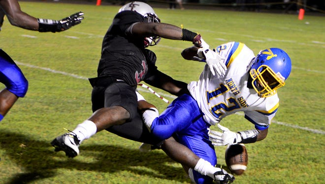 Liberty Tech's Alec Long forces North Side's Dexter Pirtle to fumble during their game last season.