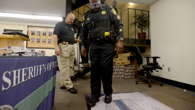 Madison County Sheriff's department Lt. Allen Castleman talks another deputy through the Fatal Vision Alcohol Impairment Simulation Friday afternoon. The Fatal Vision goggles are worn to simulate altered vision and coordinates effects of alcohol.