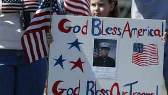 Emily Von Bulow, 8, of Wall Township, holds up a homemade poster to honor her cousin, Marine Lance Cpl. Derek Rogers in this March 23, 2003 photo – the same week the United States lauched an invasion of Iraq. Von Bulow was one of several hundred civilians who gathered outside the main gate of Naval Air Engineering Station Lakehurst to rally in support of American and British troops engaged in Operation Iraqi Freedom.
