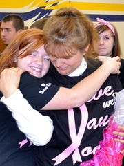 Lisa Tousey gets a hug from a student after the assembly.