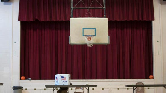 A voter fills out a ballot in the gymnasium at the