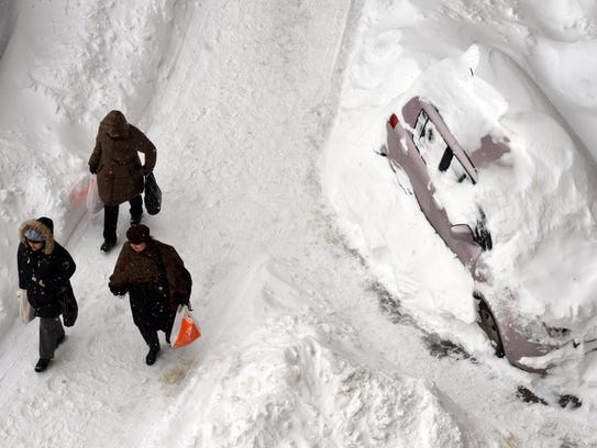 People walk along a snow-covered road in the Ukraine