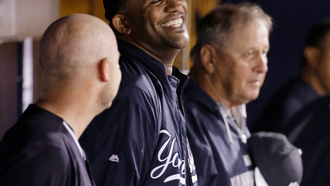 Yankees starting pitcher CC Sabathia, center, laughs as he talks with Yankees catcher Brian McCann, left, in the dugout after pitching seven innings in the Yankees' 4-0 shutout of the Pittsburgh Pirates in an exhibition game in Tampa, Fla., on Friday.
