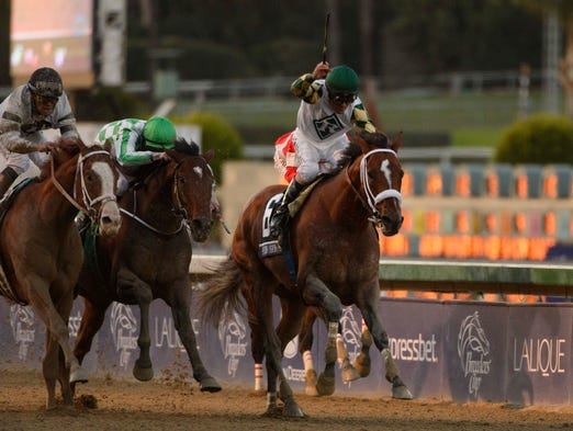 Gary Stevens aboard Mucho Macho Man comes down the stretch to win the Breeders' Cup Classic.