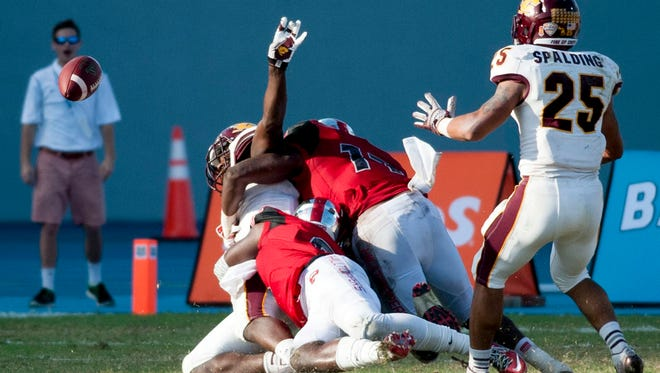 Central Michigan tight end Deon Butler laterals the ball while being tackled by Western Kentucky linebacker Dejon Brown  and defensive back Marcus Ward, foreground, during the Bahamas Bowl as part of a 75-yard touchdown.