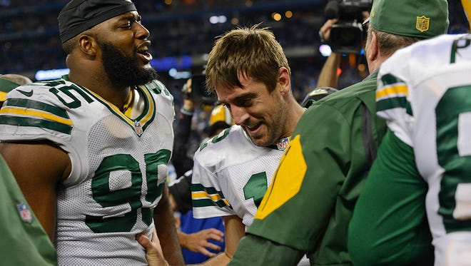 Green Bay Packers quarterback Aaron Rodgers is mobbed by his teammates after he threw a Hail Mary against the Detroit Lions to win the game Thursday night's game at Ford Field in Detroit, Mich.