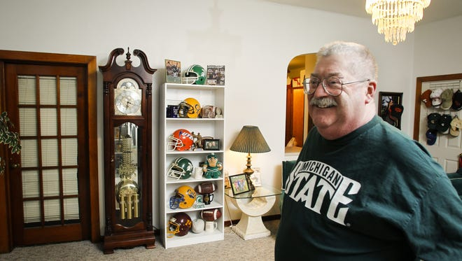 Arv Pettit, at age 65 in December of 2015, in his Grand Ledge home among his vast collection of sports memorabilia.  Pettit, a beloved former football coach at Grand Ledge High School, died Nov. 29 at 67.