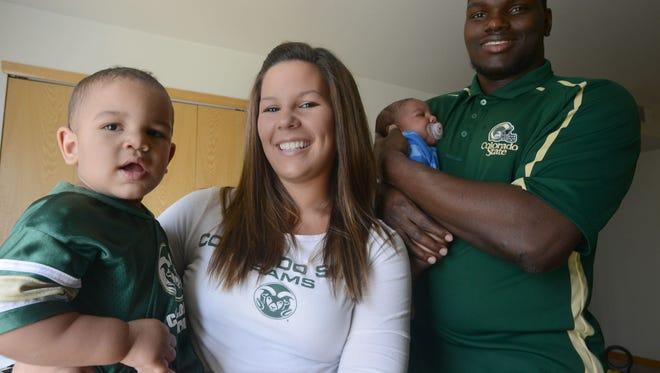 CSU linebacker, Shaquil Barrett, right, holds his son, Braylon, 6 weeks, as his wife, Jordanna Barrett, holds other son, Shaquil Jr., 1,  on July 10, 2013.