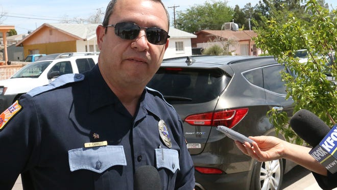 Enrique Carrillo of the El Paso police department explains a car jacking incident that occurred Monday morning. The vehicle, a Hyundai Santa Fe in background, was abandoned  by a male suspect along with its female driver along the 7300 block of Kingman.