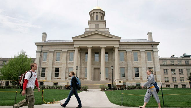 In this May 3, 2006, file photo, University of Iowa students walk past the Old Capitol building in Iowa City, Iowa, a few days before the building was to open to the public for the first time since being heavily damaged in a fire on Nov. 20, 2001.