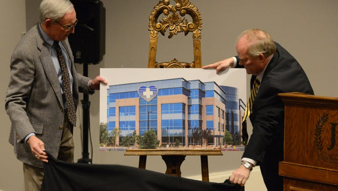 Dr. Arthur Grimball and Bob Arrington reveal concept art Monday evening of what they hope to be a new heart hospital in Jackson.