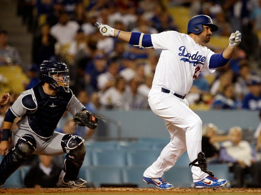 FILE - In this Sept. 26, 2017, file photo, Los Angeles Dodgers' Adrian Gonzalez, right, follows through on his double with San Diego Padres catcher Luis Torrens watching during the second inning of a baseball game, in Los Angeles. (AP Photo/Alex Gallardo, File)
