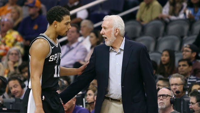 San Antonio Spurs head coach Gregg Popovich, right, talks with Spurs' guard Bryn Forbes during the second half of an NBA basketball game against the Phoenix Suns, Saturday, Dec. 9, 2017, in Phoenix. The Spurs defeated the Suns 104-101.