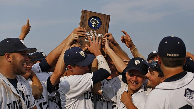 Bay Port players jump around as they hoist their trophy after defeating Green Bay Preble in Tuesday's WIAA Division 1 sectional championship game at VandenPlas Field in Green Bay.