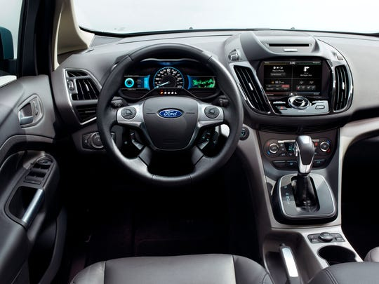 Inside the 2014 Ford C-MAX Hybrid, audio and nav controls sit high in a dash pod with climate below. The dashboard could host a picnic, but wide expanses of windshield and overhead glass invite sunlight.
