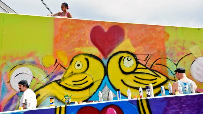 Shekirah Smith of York, top, spray paints as UpCollective York founders Copper James, bottom left, and Jimmy Purkey, bottom right, work on the wall during the Penn Street Art Bridge Launch Party on the north side of the North Penn Street bridge near Smyser Street Saturday, July 29, 2017, in York. UpCollective York and York Time Bank collaborated to turn the bridge, which has long been a target of graffiti, into a public art space that anyone can transform with paint.