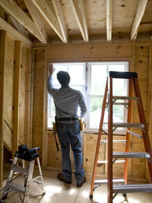 Photo illustration of a contractor working on window in new home