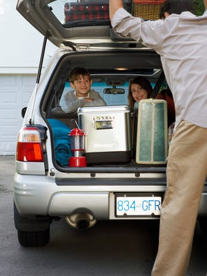 Boy and girl (8-13 years) in back seat of car, smiling at father, rear view, closing boot lid