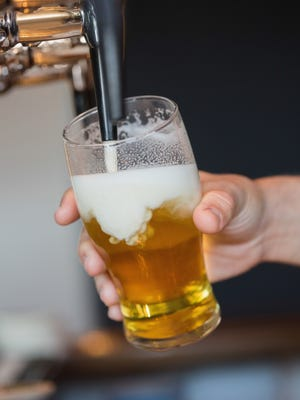 Hand holding glass filling beer.