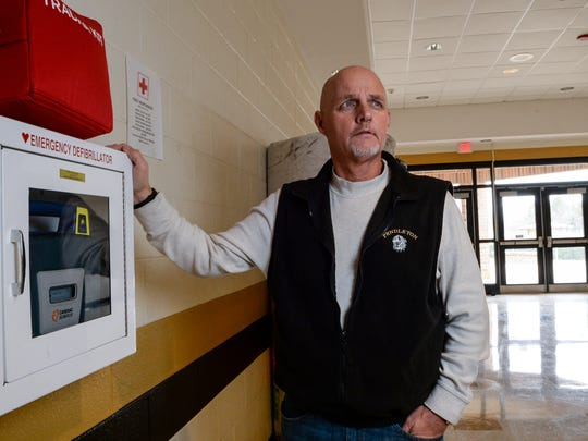 Paul Sutherland, Pendleton High School football coach, stands by an AED as he returns to his workplace 12 weeks after his heart attack in September.