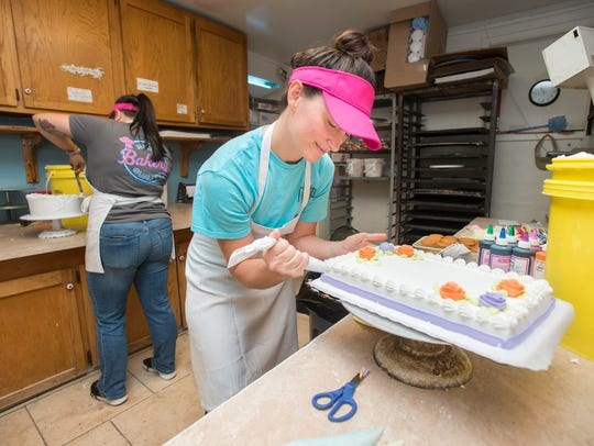 Julia Atabey, right, decorates a cake at the Milton