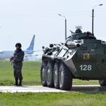 Ukrainian soldiers stand guard near an armoured personnel carrier (APC) during US Vice President's visit at the Boryspil airport in Kiev on April 21, 2014.