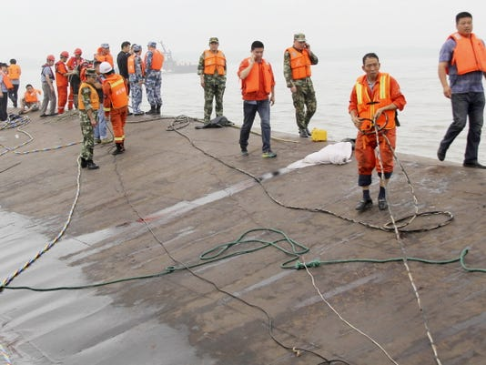 Rescue workers walk on the hull of a capsized cruise ship on the Yangtze River in Jianli in central China's Hubei province Tuesday, June 2, 2015.