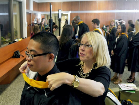 York College admissions associate director Cortnie Amelotte helps soon-to-be graduate Linh Pham with his regalia before commencement.