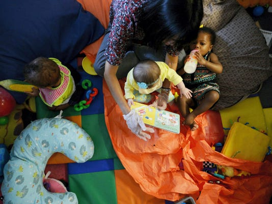 Lead infant teacher Chayanee Propst reads with children Sa'Nya McNealy, left, Sutton Brillhart, and Lillianna Lowe at the YWCA York. Propst grew up in the jungles of Northern Thailand, and her parents instilled in her a firm belief in the importance of education.