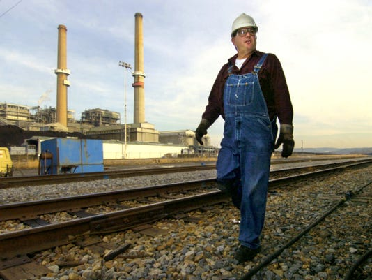 KRISTIN MURPHY — DAILY RECORD/SUNDAY NEWS Randy Starner, a railroad inspector for Norfolk Southern, walks the right-of-way in front of PPL's Brunner Island Power Plant while inspecting a coal train in this 2006 file photo.