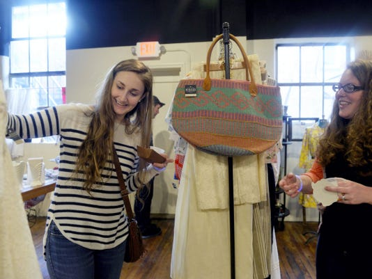 Megan Meckley of Washington Townsip, left, shows a vintage dress to Katie Callahan of West Manchester Township at Redeux Marketplace during the Royal Square Beer Crawl April 17. Redeux will let customers create their own bouquets as part of First Friday.