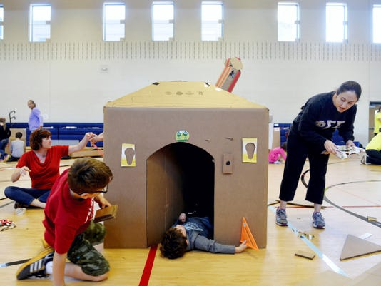 Michael Tansey, 7 of Spring Garden Township, left, works on a doorknob for a cardboard house occupied by Elliott Lewis, 5 of Spring Garden Township, as Lewis's mother Liz cuts up boxes to make roof shingles during York's first Global Cardboard Challenge on Saturday.