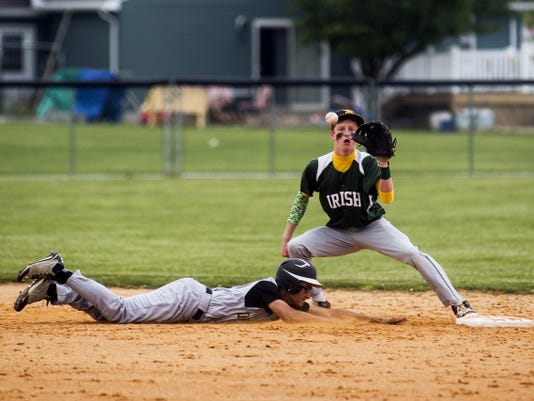 York Catholic's Brenden Kennedy reaches for a catch as Delone Catholic's Cody Pfaff slides during a pick-off attempt Thursday in a District 3 Class AA baseball quarterfinal Thursday at Delone Catholic. York Catholic won, 2-1.