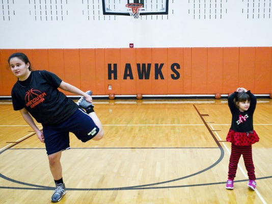 Hanover girls' basketball sophomore Zaynah Tracy (left) stretches before practice alongside head coach Denny Garman's 5-year-old daughter Ava