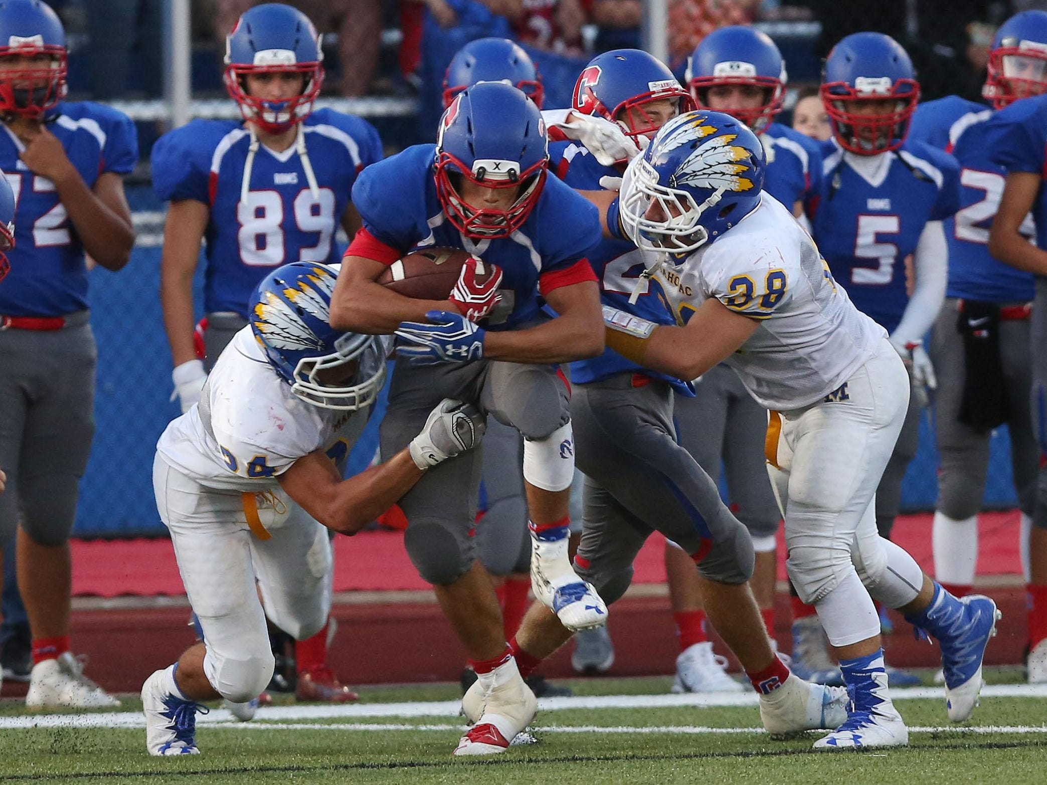 Carmel's David Vega tries to break away from Mahopac's Robert Hoyt, left, on a first-half run during Friday's game at Carmel High School.