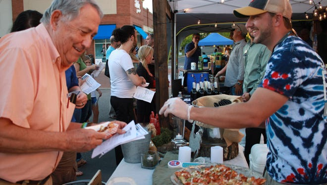 Andy Barrett grabs a slice of pizza from Zach Olds of Sander's Ferry Pizza at A Taste of Hendersonville on Thurs. Sept. 28, 2017.