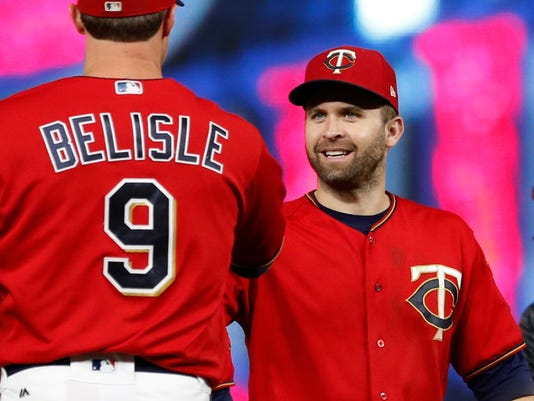 Minnesota Twins pitcher Matt Belisle, left, and teammate Brian Dozier celebrate the Twins' 6-3 win over the Detroit Tigers in a baseball game Friday, Sept. 29, 2017, in Minneapolis. Dozier had three RBIs. (AP Photo/Jim Mone)