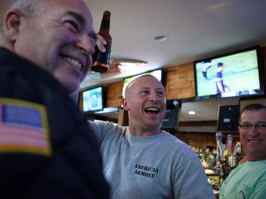 Asbury Park Fire Fighter Cortland Heyniger raises his beer. Woody's Tavern in Farmingdale didn't show football on Sunday in respect for veterans on Veterans Day weekend. In place of the games, the bar will hold a special concert featuring members of the New Jersey-based country group After the Reign, with a portion of the proceeds going to the Green Beret Foundation through Special Forces Association Chapter 19. Farmingdale, New Jersey. Sunday, November 12, 2017. David Gard