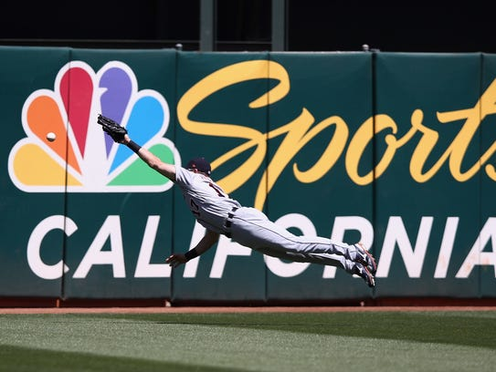 Andrew Romine of the Detroit Tigers dives, but can