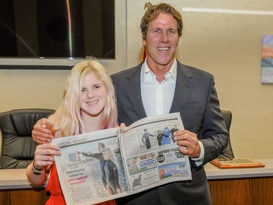 Juno Beach Civic Association Citizen of the Year William Kimball stands with Ruthie Nash, displaying a story in the Jupiter Courier Newsweekly about their recent surfing collaboration.