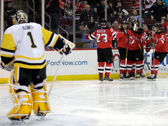 Pittsburgh Penguins goaltender Casey DeSmith, left, stands in the crease as New Jersey Devils celebrate a goal by Travis Zajac (19) during the second period of an NHL hockey game Saturday, Feb. 3, 2018, in Newark.