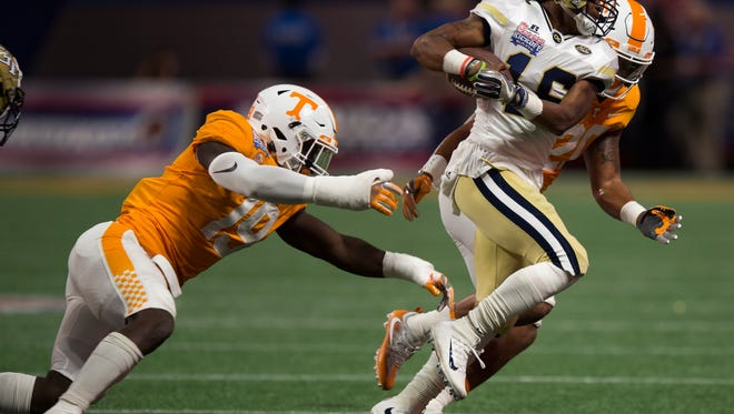 Tennessee defensive lineman Darrell Taylor (19) and Tennessee linebacker Cortez McDowell (20) tackle Georgia Tech quarterback TaQuon Marshall (16) during the Chick-fil-A Kickoff Game at the Mercedes-Benz Stadium in Atlanta on Monday, Sept. 4, 2017.