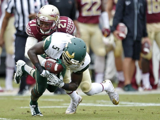 FSU's Marquez White tackles USF's Marlon Mack during their game at Doak Campbell Stadium on Saturday.