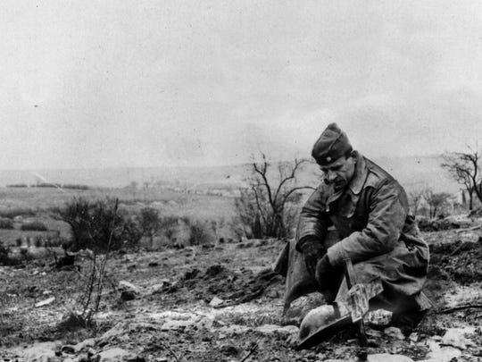 An officer pauses by the grave of Lt. Robert E. Bentley of Cincinnati, killed in action at Cierges, France, on Sept. 28, 1918.