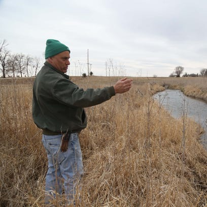 Mark Schleisman, of Lake City, points out where a saturated