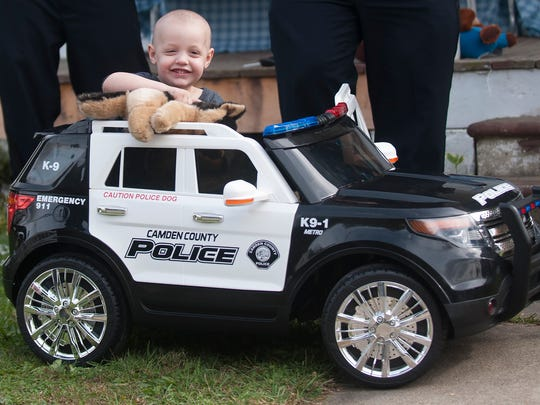 Ben Graham age 3, smiles in his new K-9 Police car Monday, Oct. 23, 2017, in Elmer Township, N.J. Camden County Police surprised Ben with a special K9 demo and his own little police car. Ben has neuroblastoma, and he loves police and police dogs.