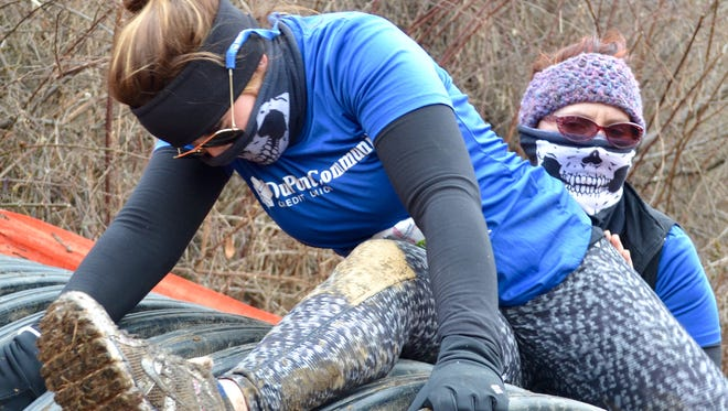 Heather Farrar, 28, of Waynesboro gets a helping hand from her friend Kim Cullen, 50, of Staunton during the Mad Anthony Mud Run in Waynesboro.