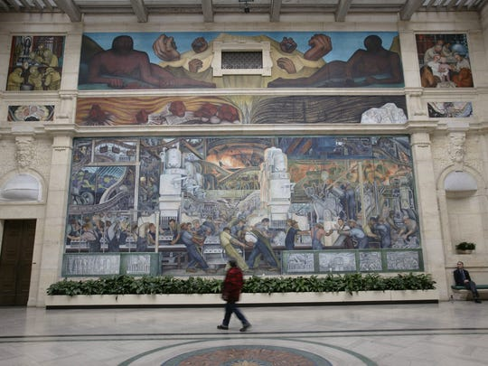 Visitors in the Rivera Court at the Detroit Institute of Arts, view Detroit Industry, painted by Diego Rivera.