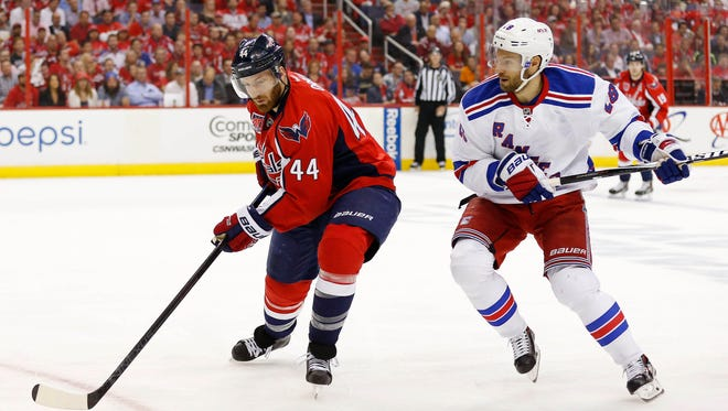 Washington Capitals defenseman Brooks Orpik (44) and New York Rangers center Dominic Moore (28) battle for the puck in the first period in game four of the second round of the 2015 Stanley Cup Playoffs at Verizon Center.